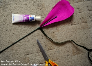 Get a teardrop petal and wrap it around the bottom of the stem. Use the floral tape and glue to secure it.